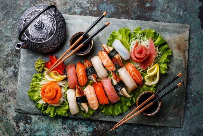Sushi Set nigiri and sashimi with tea. Served on gray stone slate on metal background