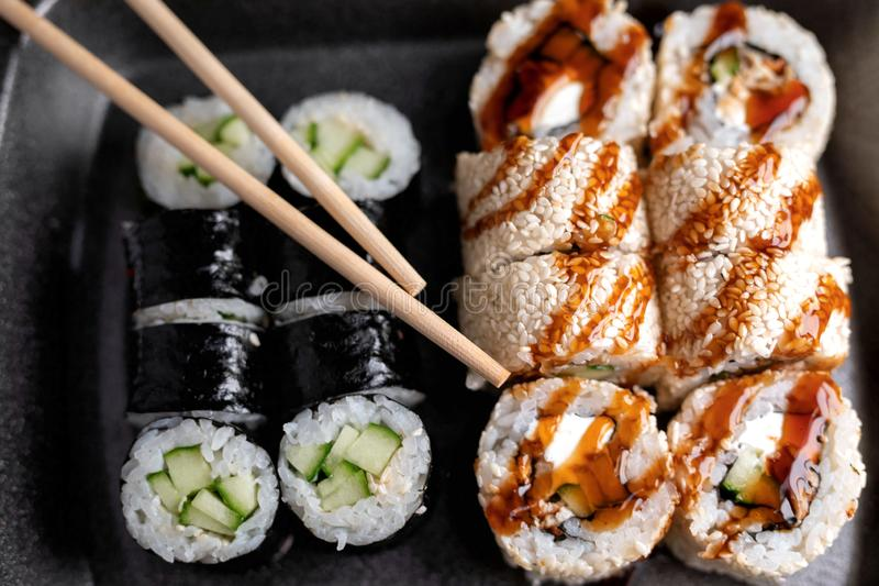 Sushi Set rolls in plastic food delivery box with chopsticks. Top view. Japan menu. Sushi Set rolls in the plastic food delivery box with chopsticks. Top view stock photo