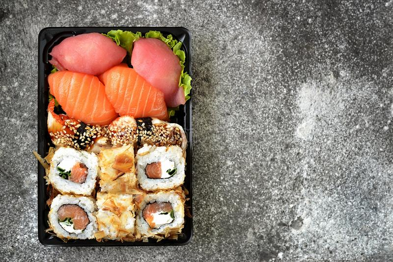 Sushi set with salmon, soft cheese, tuna, smoked eel. Sushi delivery to home. Healthy food. Top view. Food royalty free stock image