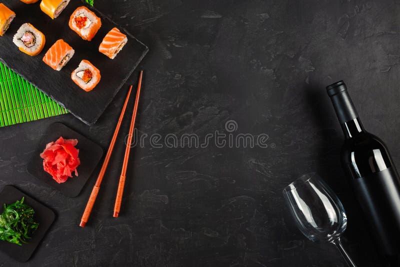 Sushi Set sashimi and sushi rolls, bottle of wine and a glass served on stone slate royalty free stock photos