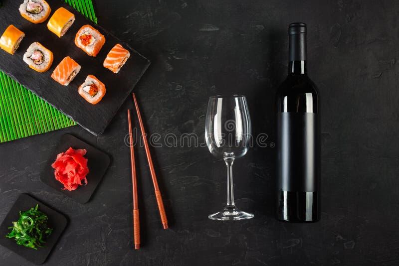 Sushi Set sashimi and sushi rolls, bottle of wine and a glass served on stone slate stock images