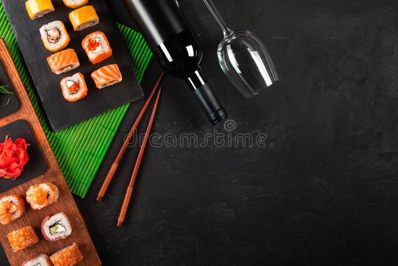 Sushi Set sashimi and sushi rolls, bottle of wine and a glass served on stone slate royalty free stock photography