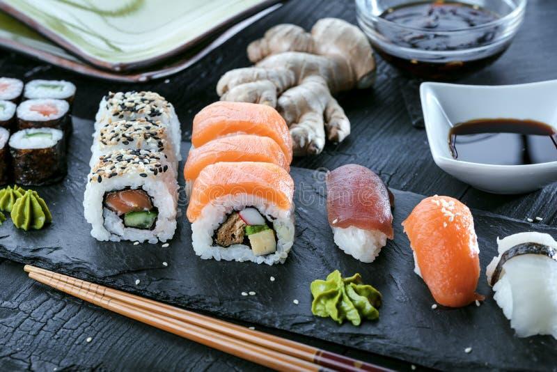 Sushi Set sashimi and sushi rolls served on stone slate. stock photos