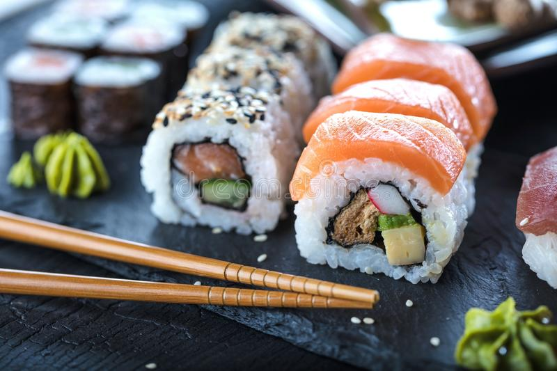Sushi Set sashimi and sushi rolls served on stone slate. stock images