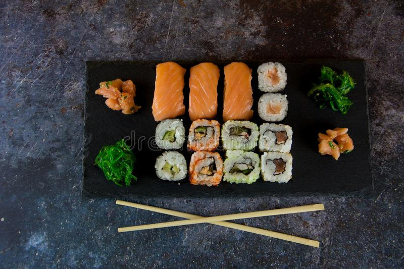 Sushi Set sashimi and sushi rolls served on stone slate stock images