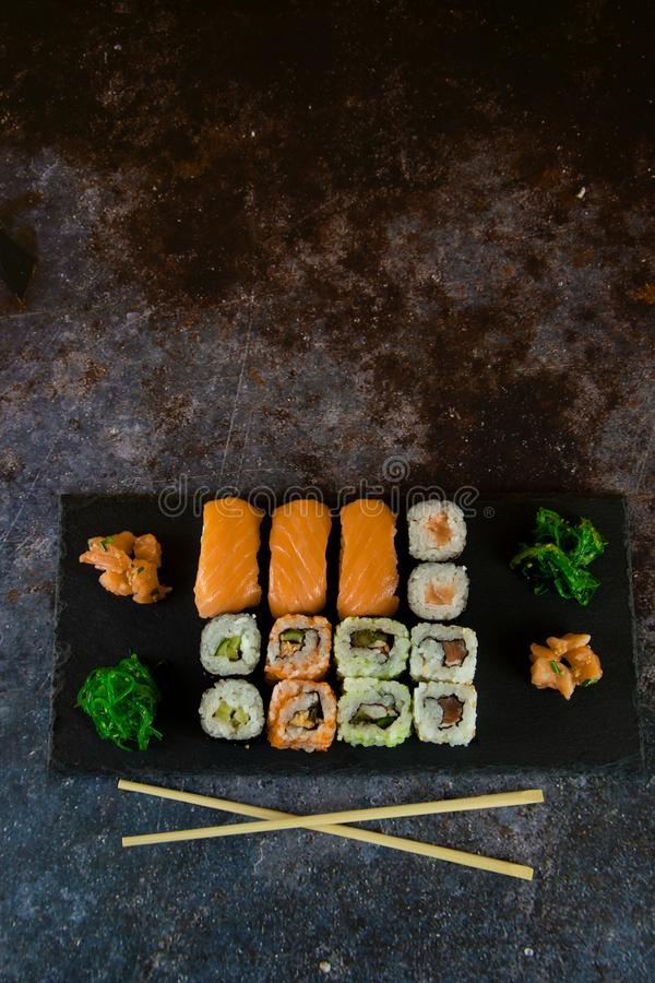 Sushi Set sashimi and sushi rolls served on stone slate royalty free stock photo