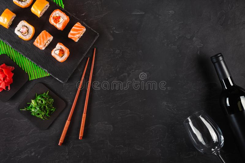 Sushi Set sashimi and sushi rolls, bottle of wine and a glass served on stone slate stock photo