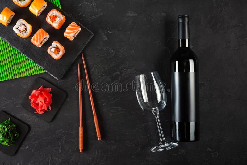 Sushi Set sashimi and sushi rolls, bottle of wine and a glass served on stone slate royalty free stock photo