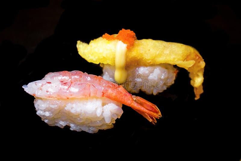 Sushi Set Sashimi and sushi rolls served on black stone slate. stock image
