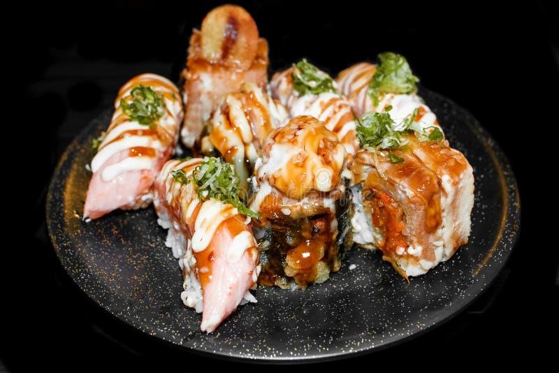 Sushi Set Sashimi and sushi rolls served on black stone slate. royalty free stock images