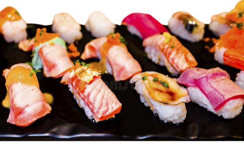 Sushi Set sashimi and sushi rolls served on black stone slate. stock photos