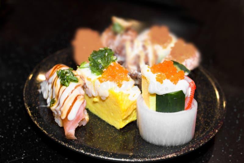 Sushi Set Sashimi and sushi rolls served on black stone slate. royalty free stock image