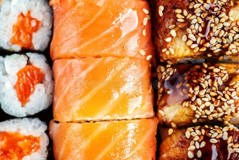 Sushi Set sashimi and sushi rolls served on dark plate. Image of Japanese food on dark background. stock photography