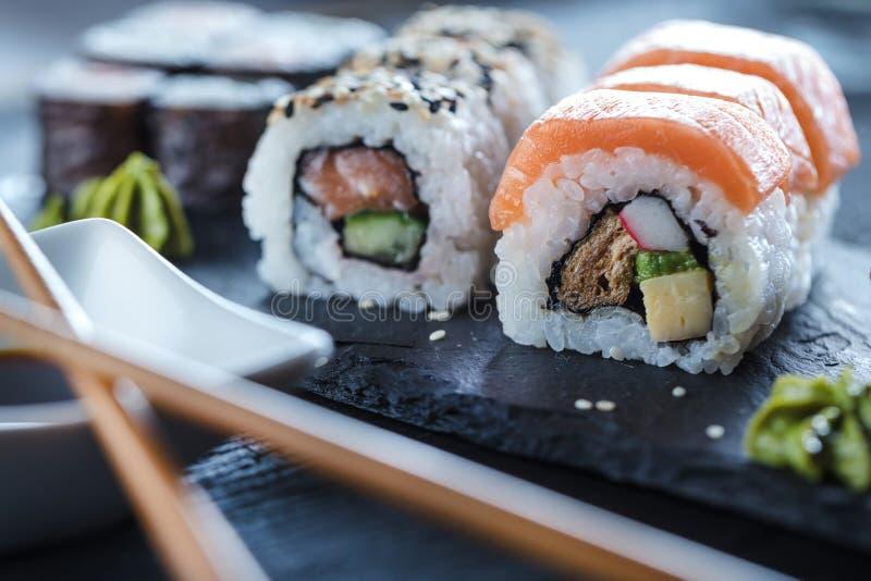 Sushi Set sashimi and sushi rolls served on stone slate. stock photography