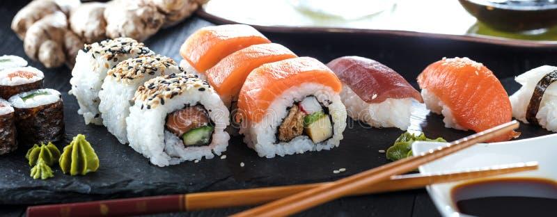 Sushi Set sashimi and sushi rolls served on stone slate. stock images