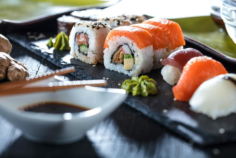 Sushi Set sashimi and sushi rolls served on stone slate. royalty free stock photos