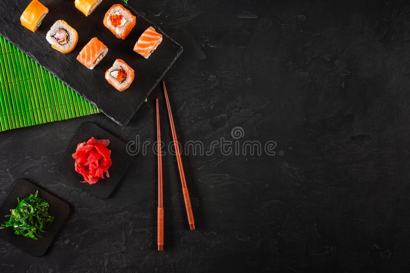 Sushi Set sashimi and sushi rolls served on stone slate royalty free stock image