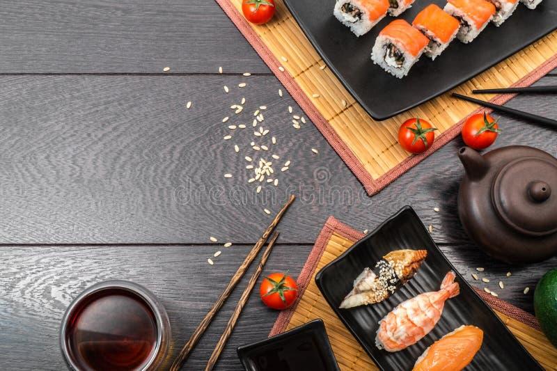 Sushi set sashimi and sushi rolls and tomatoes served on dark background stock photos