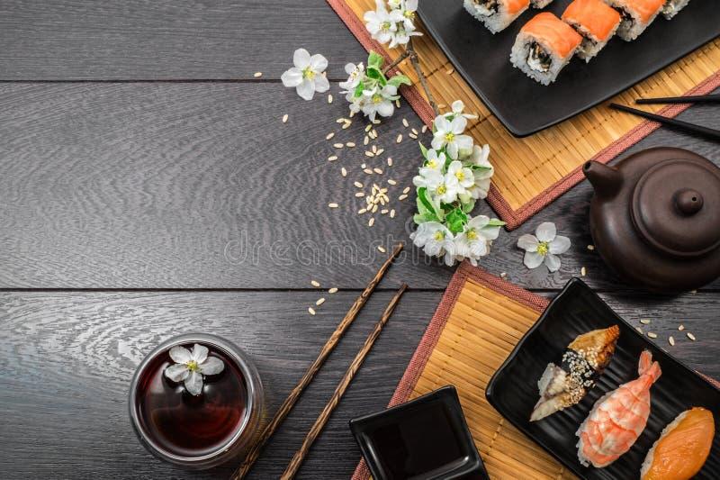 Sushi set sashimi and sushi rolls and white flowers on dark background stock photography