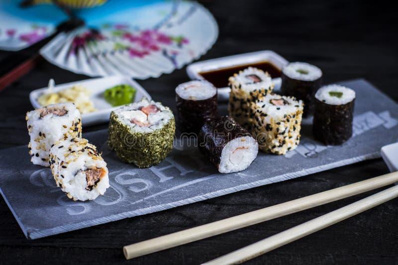 Sushi Set served on black stone slate on black wooden background stock photos