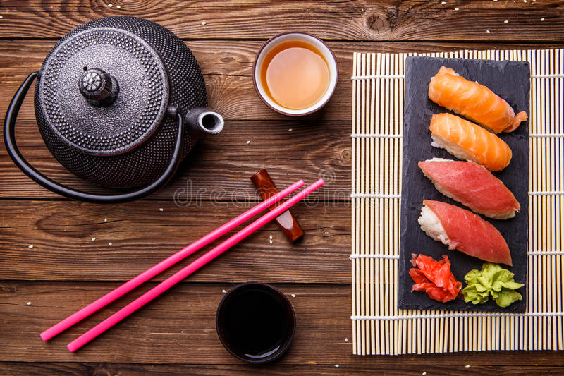 Sushi Set served on gray stone slate with soy sauce, grey teapot and cup of tea stock image