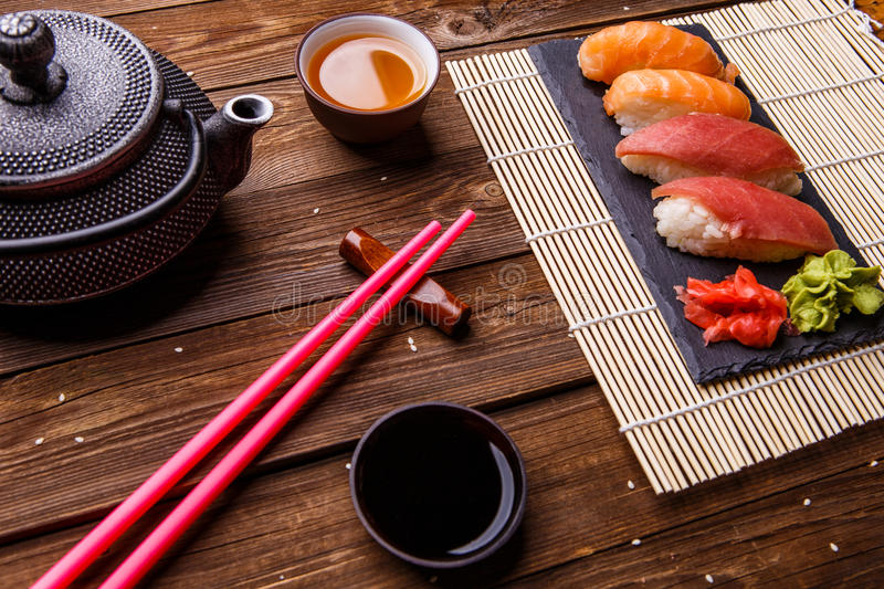 Sushi Set served on gray stone slate with soy sauce, grey teapot and cup of tea stock images