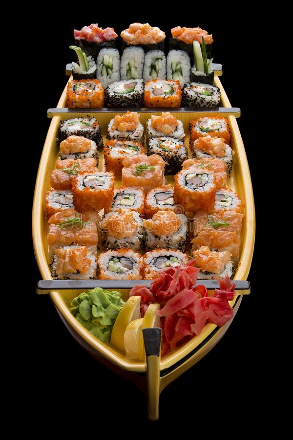 Sushi set in a wooden boat on a black background.  royalty free stock photography