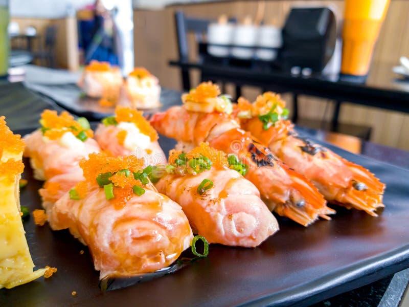 Sushi Shrimp burn the fire Aburi River Prawn and Aburi Salmon sushi with sauce and Tamagoyaki Sandwich put on a black plate in J royalty free stock image