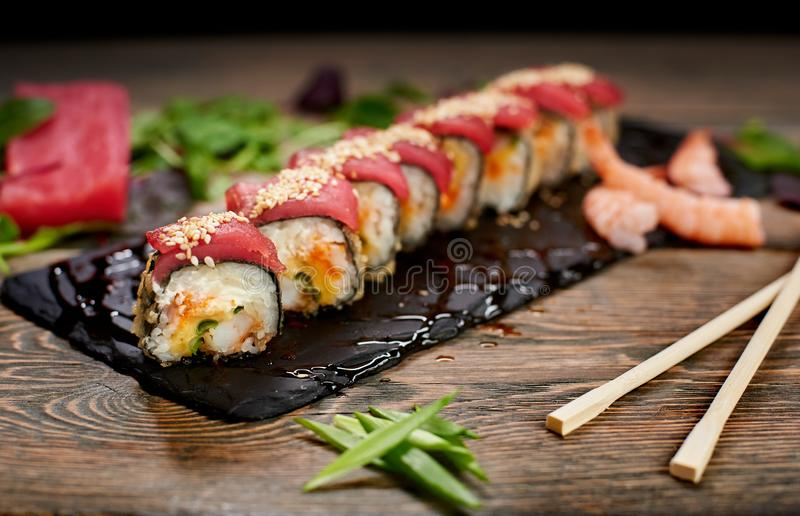 Sushi on sloppy lubricate stone plate. Focus on details. Front view. Chopsticks on wooden table. Blurred background. Sushi covered with tuna and sesame seeds on stock photos