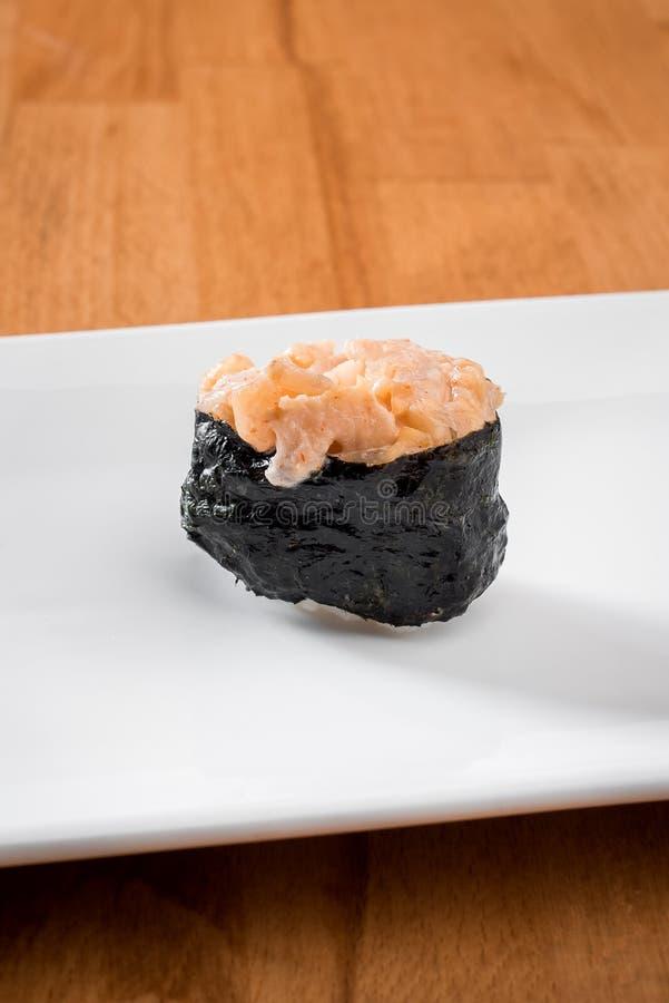 Sushi som är gunkan med krabban som isoleras på den vita plattan på en träbakgrund close upp avstånd fotografering för bildbyråer