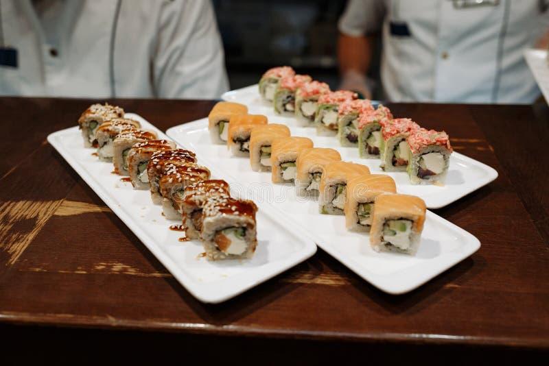 Sushi stellt auf rechteckige Platten auf einem Holztisch ein stockbild