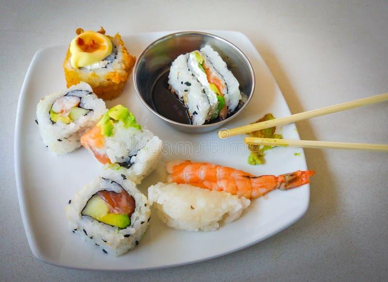 Sushi sul piatto bianco con i bastoncini immagine stock
