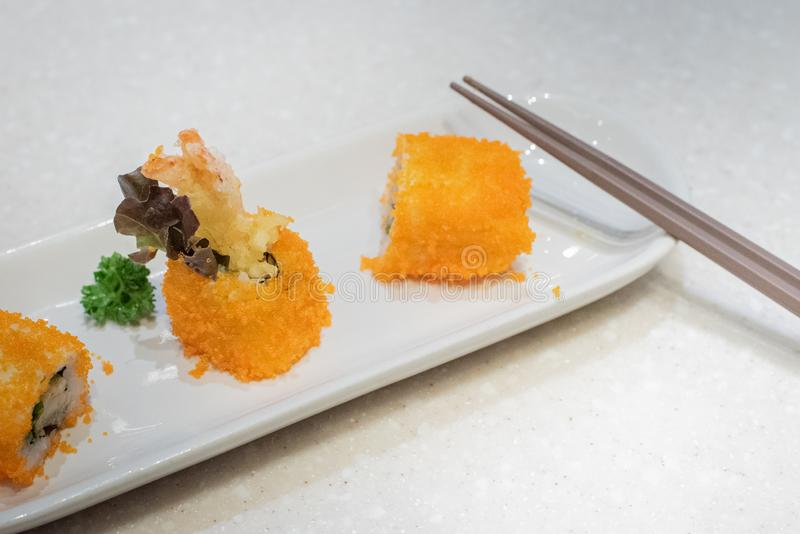 Sushi tempura shrimp eggs vegetables on dish with chopsticks on table. Japanese food stock photo