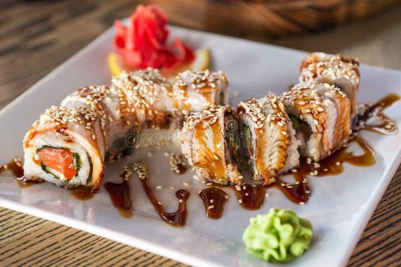 Sushi und Rollen in der Platte auf einem Holztisch Sushimenü Japanische Nahrung lizenzfreie stockfotos