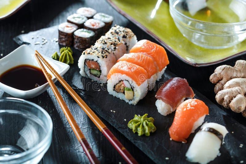 Sushi Vastgestelde die sashimi en sushibroodjes op steenlei wordt gediend stock afbeelding