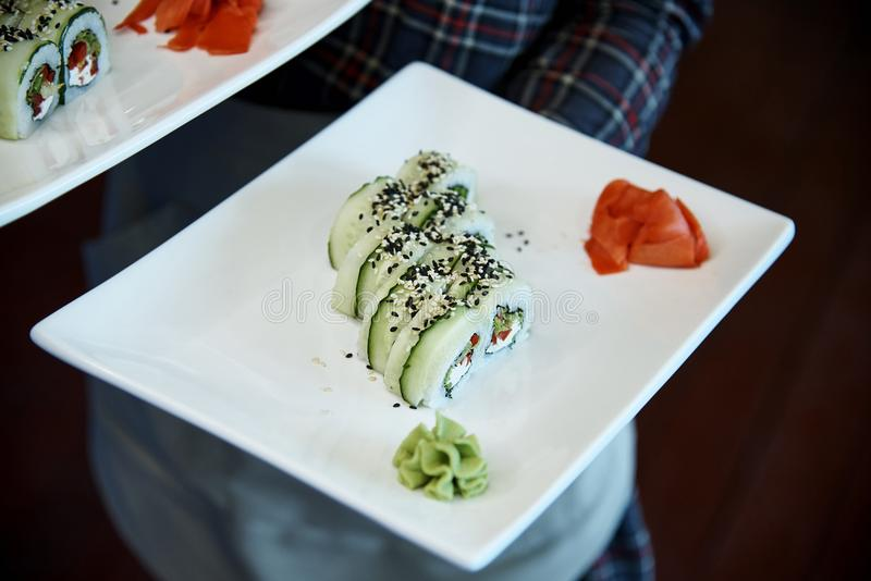 Sushi. On a white plate in the hands of the waiter stock photos