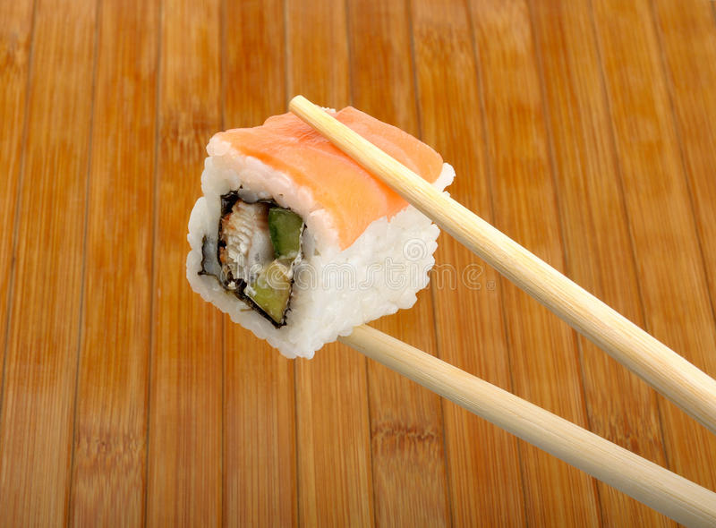 Sushi in wooden chopsticks. Sushi fish in wooden chopsticks in the background mat stock photo