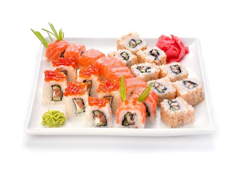 Sushi y rodillo en placa imagen de archivo