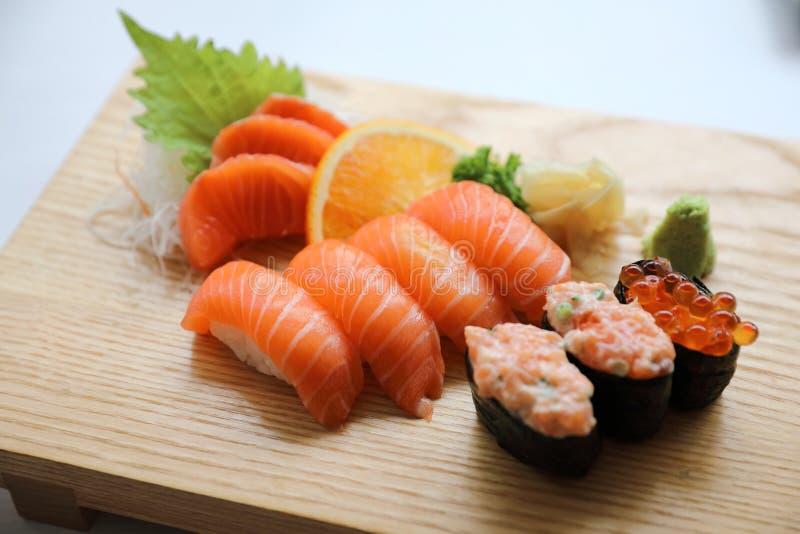 Sushi y sashimi de color salmón en la comida japonesa de la placa de madera imagen de archivo