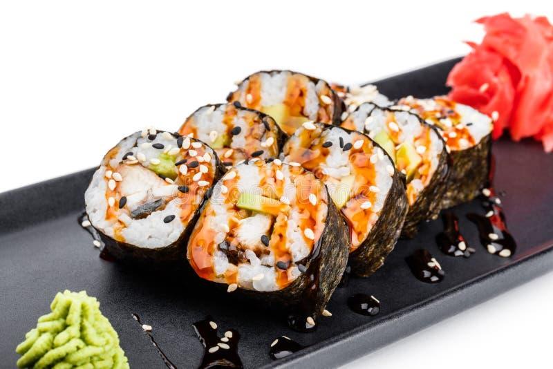 Sushibroodje - Maki Sushi van gerookte paling, Krabvlees, avocado op zwarte die plaat wordt over witte achtergrond wordt geïsolee stock fotografie