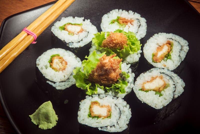 Sushibroodje met kip en sla op zwarte plaat stock fotografie