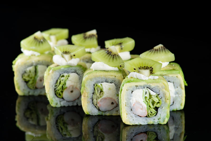Sushibroodje met krabvlees, kiwi en avocado over zwarte backgrou stock foto's