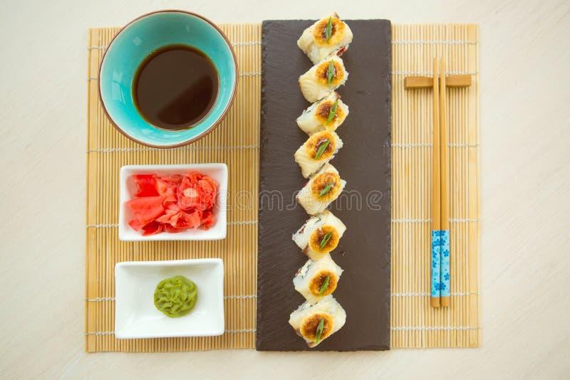 Sushibroodjes die op een steenplaat worden gediend in een restaurant Gebraden heet Broodje met zalm, avocado, komkommer royalty-vrije stock afbeeldingen
