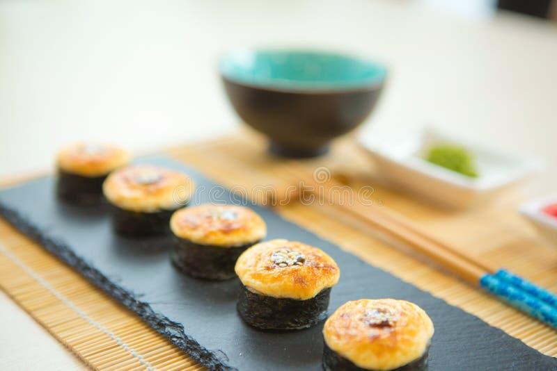 Sushibroodjes geplaatst die op grijze steenlei worden gediend op metaalachtergrond stock foto's