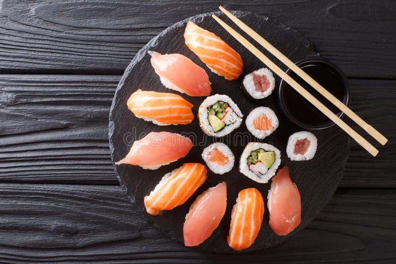 Sushibroodjes geplaatst die op zwarte steenlei worden gediend op donkere achtergrond stock fotografie