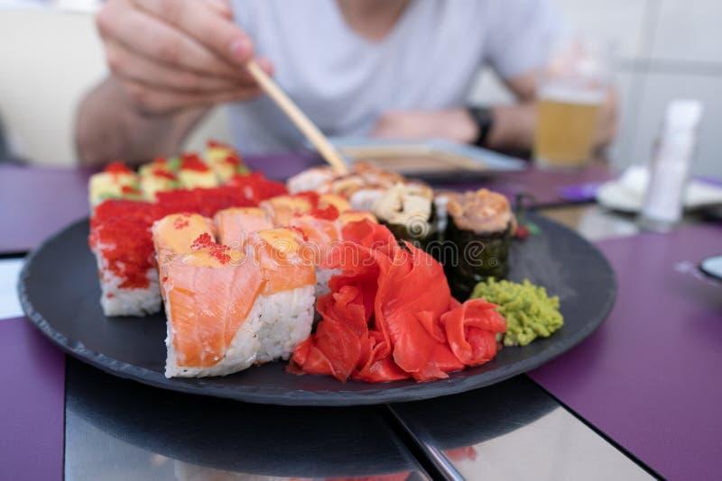 Sushiclose-up De kerel eet sushi en broodjes met eetstokjes stock foto's