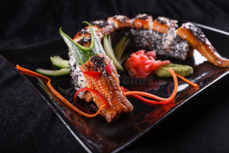Sushidrake med ålen, gurkan och avokadot på en svart bakgrund Japansk mat som är smaklig av mål för lunch royaltyfri bild