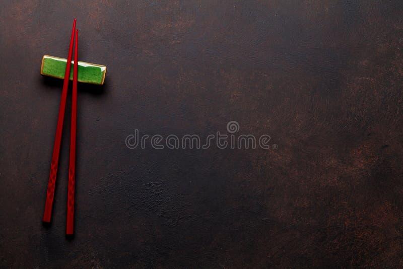 Sushiessstäbchen auf Steintabelle lizenzfreies stockfoto