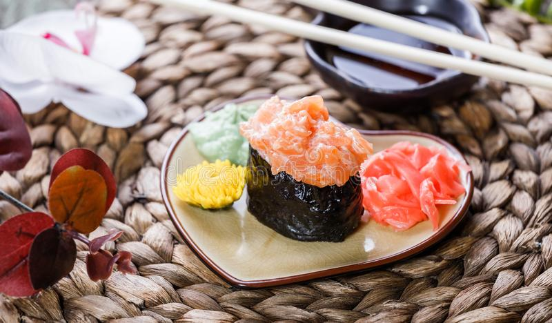 SushiGunkan maki med laxen på plattan på mattt för bambu som dekoreras med blommor Japansk kokkonst royaltyfri bild
