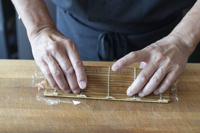 Sushikock som rullar upp sushi i ett mattt arkivbild
